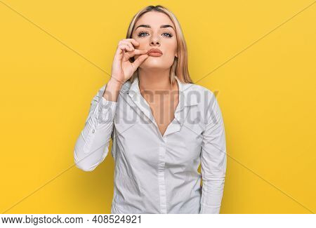 Young caucasian woman wearing casual clothes mouth and lips shut as zip with fingers. secret and silent, taboo talking