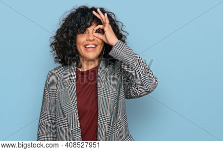 Young hispanic woman wearing business clothes doing ok gesture with hand smiling, eye looking through fingers with happy face.