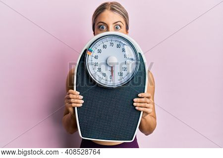 Beautiful blonde woman holding weight machine to balance weight loss making fish face with mouth and squinting eyes, crazy and comical.