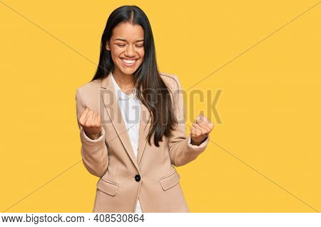 Beautiful hispanic woman wearing business jacket very happy and excited doing winner gesture with arms raised, smiling and screaming for success. celebration concept.