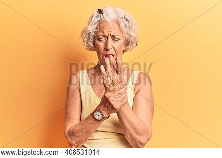 Senior grey-haired woman wearing casual clothes suffering pain on hands and fingers, arthritis inflammation