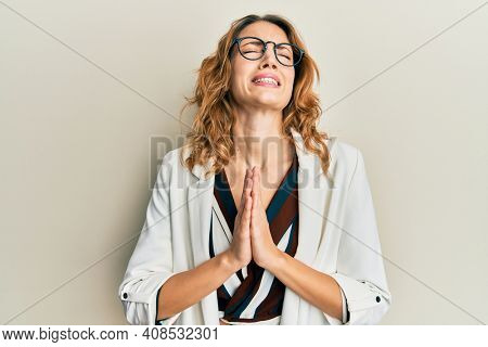 Young caucasian woman wearing business style and glasses begging and praying with hands together with hope expression on face very emotional and worried. begging.