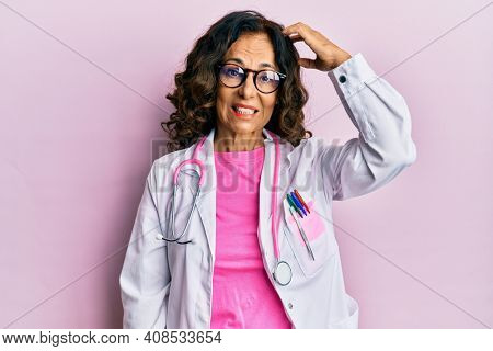 Middle age hispanic woman wearing doctor uniform and glasses confuse and wonder about question. uncertain with doubt, thinking with hand on head. pensive concept.
