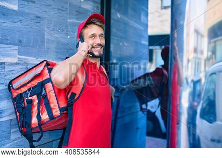Caucasian delivery man wearing red uniform and delivery backpack smilly happy outdoors speaking on the phone
