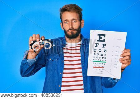 Handsome caucasian man with beard holding optometry glasses and eyesight test depressed and worry for distress, crying angry and afraid. sad expression.