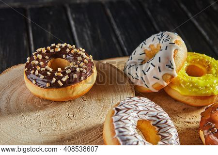 Multicolored Donuts With Glaze And Sprinkles On Wooden Coasters On A Black Background
