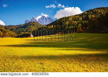 San Giovanni church in St. Magdalena village. Location place Val di Funes (Villnob), Dolomite alps, Trentino-Alto Adige, Italy, Europe. Image of popular world landmarks. Discover the beauty of earth.