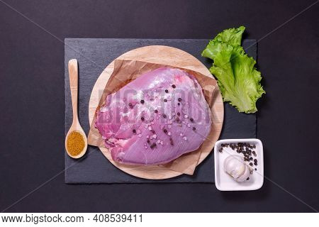 Raw Fresh Turkey Breast Fillet With Seasonings On A Black. The View From The Top, Flat Lay
