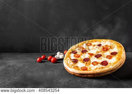 Traditional Italian Pizza With Mozzarella, Tomatoes And Salami. Hot Pizza Just From Oven, Black Back