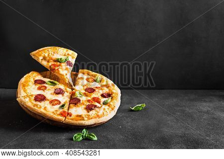 Traditional Italian Pizza With Mozzarella, Tomatoes And Salami. Fresh Slices Pizza Over Black Backgr