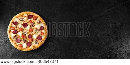 Supreme Pizza With Pepperoni, Mushrooms And Mozzarella Cheese On Black Table, Top View, Copy Space.