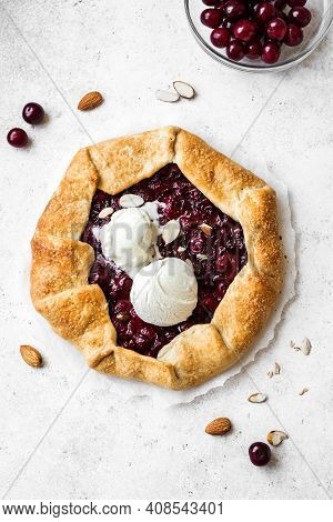 Cherry Galette With Almonds And Vanilla Ice Cream On White, Top View, Copy Space. Homemade Healthy D