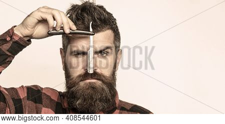 Handsome Bearded Hairdresser In Stylish Wear Is Holding A Straight Razor While Standing At The Barbe
