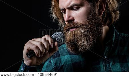 Male Attends Karaoke. Man With A Beard Holding A Microphone And Singing. Man Singing With Microphone