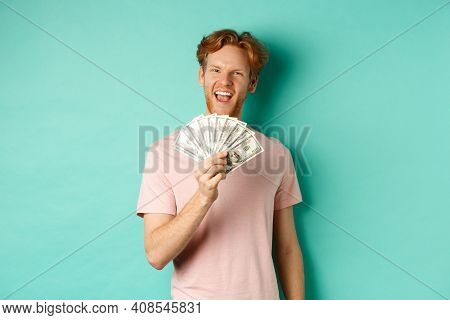Happy Redhead Man In T-shirt Showing Money In Dollars And Smiling, Making Smug Faces After Winning C