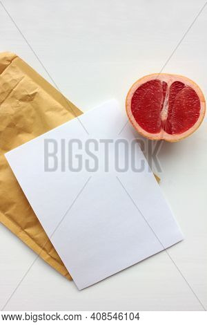 Summer Still Life With Half Of Grapefruit, Blank Paper Card. And Golden Envelope On White Background