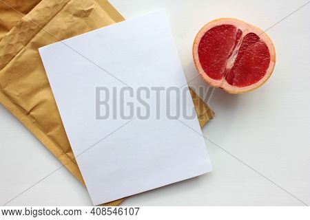 Summer Still Life With Half Of Grapefruit, Blank Paper Card And Golden Envelope On White Background.