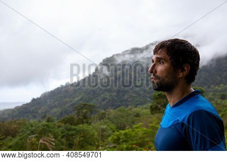 Trekker On The Mountain Landscape. A Lonely Man On The Background Of The Mountains. Trekking In The