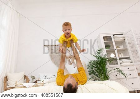 Male Parent Holds A Boy In Outstretched Arms
