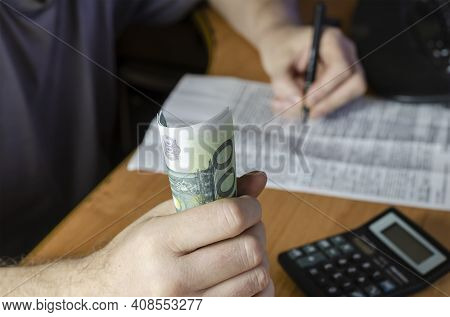 A Defocused Shot Of A Hand With Hundred Euro Bills. A Man Is Holding One Hundred Euro Bills And Hand