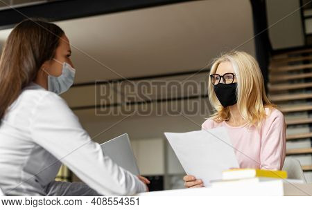 Mature Blonde Female Hr Manager Sitting At The Desk, Wearing Face Mask, Training Young Female Worker