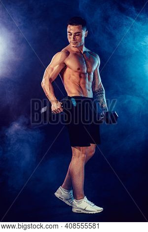 Athletic Man Flexing Muscles In Studio On Dark Background With Smoke. Strong Bodybuilder With Perfec
