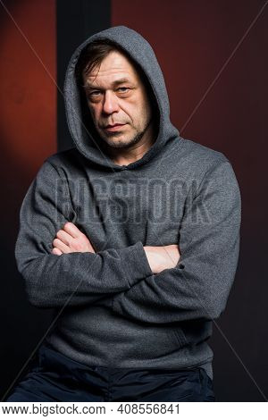 Studio Portrait Of A 40-50-year-old Serious Man In A Gray Hoodie On A Neutral Background, Eyes Direc