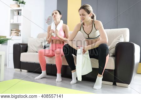 Two Tired Women Are Sitting On Couch After Fitness Workout. Home Workout And Workout Program Concept