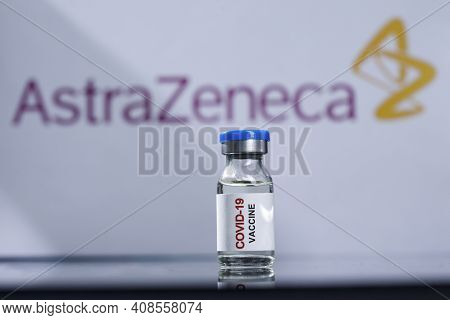 Coronavirus Vaccine Bottle Held By A Gloved Hand And In The Background The Brand Of Pharmaceutical C
