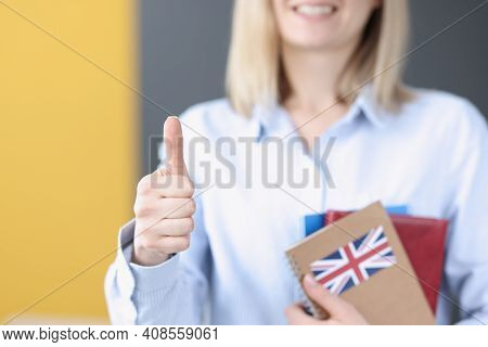 Woman Holds Textbooks With Uk Flag And Shows Thumbs Up. Higher Education In England For Foreigners C