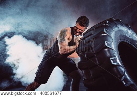 Bodybuilding Training, Bearded Strong Sportsman With Muscular Body Lifting Heavy Wheel In Gym.