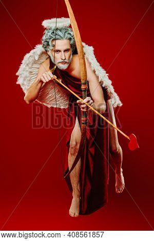 An angel who makes people fall in love. Full length portrait of a Cupid flying with the bow and arrow of love on a red background. Valentine's Day concept.