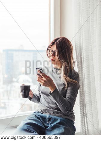 Thoughtful Woman With Eyeglasses And Cup Of Hot Coffee Looks At Her Smartphone. Information In Onlin