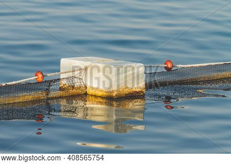 Netted Swimming Area In Sea. Net With Red Floats Is Held On Concrete Base. Sunset On Sea. Hurghada,
