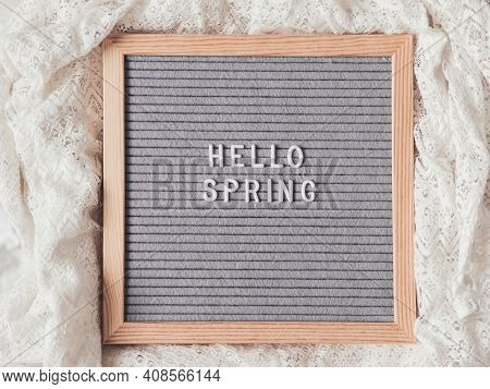 Top View On Grey Letter Board With Season Greeting Hello Spring. Crumpled White Laces. Signs On Text
