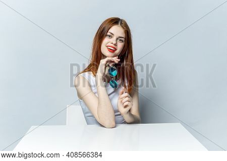 Pretty Redhead Woman With Red Lips Glamor Glasses In Hands Sitting At The Table