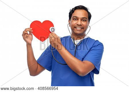 healthcare, profession and medicine concept - happy smiling indian doctor or male nurse in blue uniform with red heart and stethoscope listening to heartbeat over white background