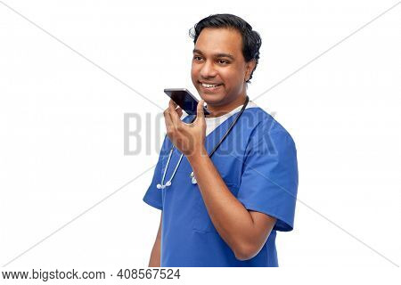 healthcare, medicine and technology concept - happy smiling indian doctor or male nurse in blue uniform using voice command recorder on smartphone over white background