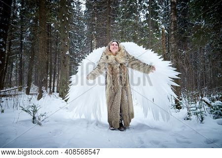A Middle-aged Woman In A Large Warm Fur Coat And White Angel Wings In A Winter Forest With Snow And