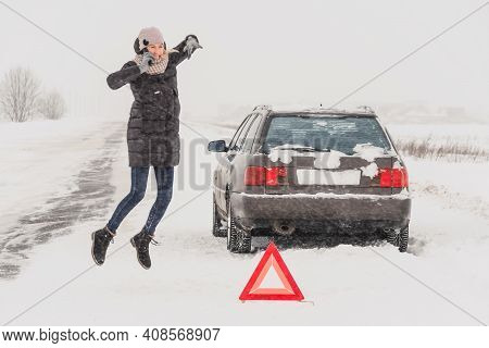 Angry Young Woman Is Talking On A Mobile Phone, Waving Her Hands In Anger Near A Warning Road Sign: