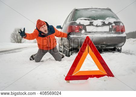 Angry Young Man In An Orange Jacket Is Kneeling On The Snow-covered Road And Shouting. He Is In A St