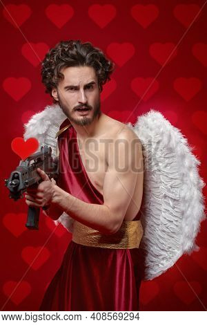 Modern Cupid with a big gun looking for a sacrifice of love. Red background. God of Love. Valentine's Day and Love.