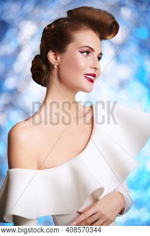 Portrait of a beautiful lady in elegant white dress. Pin-up style in clothes, hair and make-up. Festive look.
