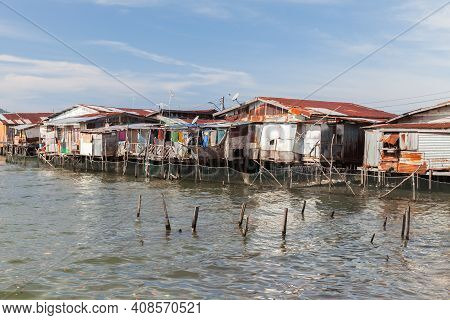 Old Wooden Rickety Houses And Footbridges On Stilts. Coastal View Of Poor Living District Of Kota Ki