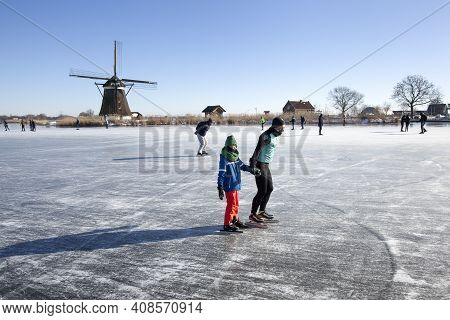 Zevenhuizen, Netherlands - February 13, 2021: Dutch Winter Landscape With Ice Skaters On The Rotteme