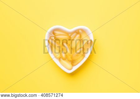Omega 3 Capsules In A Heart-shaped Plate On Yellow Background. Fish Oil Softgels. Copy Space. Top Vi
