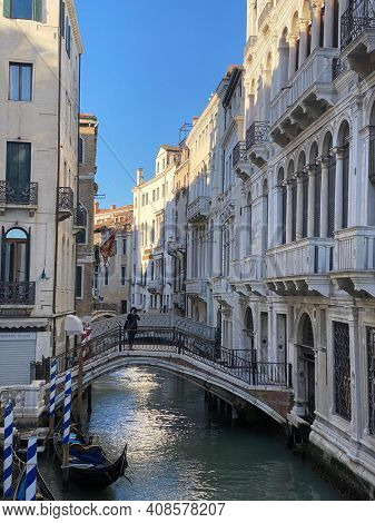 Venice, Italy, February 13, 2021 - Unrecognizable person alone taking a picture with a smart phone from a beautiful bridge over a small canal lined, on colorful building background, Venice, Italy