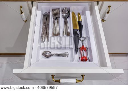 Set Of Knives, Forks And  Spoons On The Shelf In The Kitchen Cabinet
