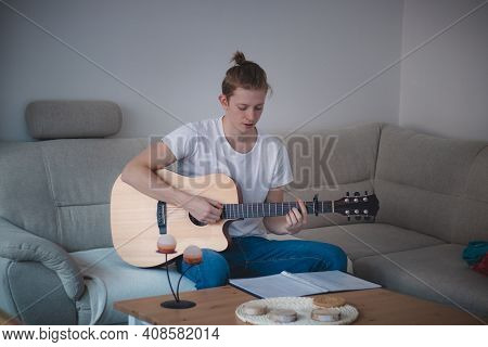 Talented Boy Playing A Wooden Acoustic Guitar In A Lighted Room. Blonde Man Aged 20-29 Strums Guitar