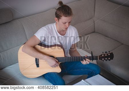 Candid Portrait Of A Young Singer Playing An Acoustic Guitar And Singing In A Hymn Book In A Lighted